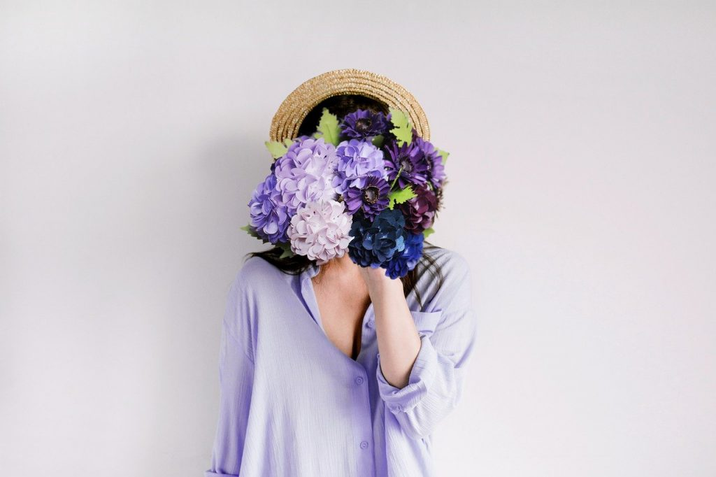 female condom - a woman holding with flowers