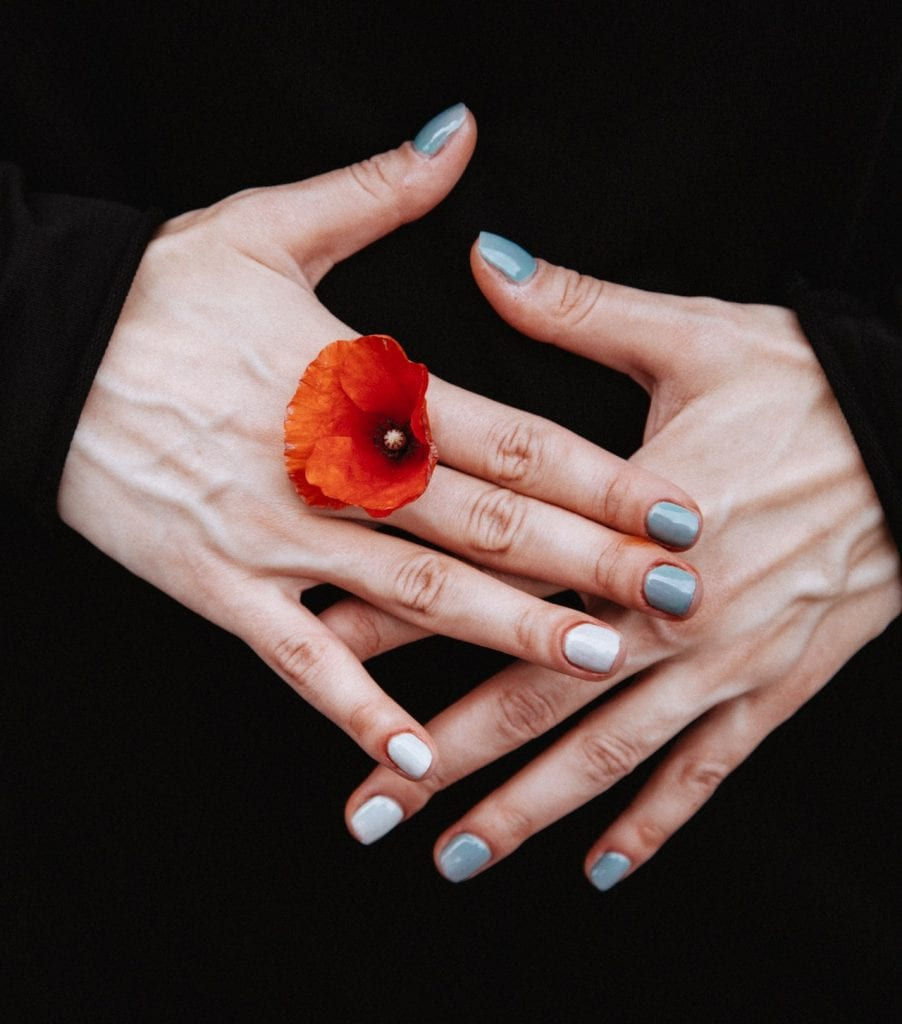 person-holding-red-petaled-flower-between-his-finger-