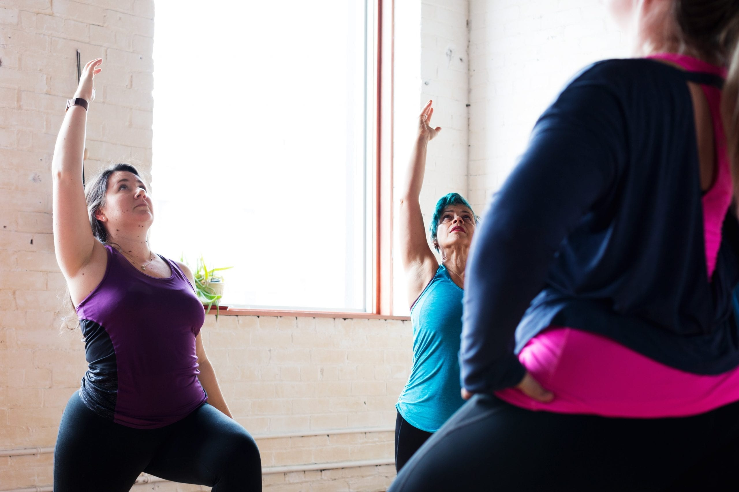 women doing yoga next to a window