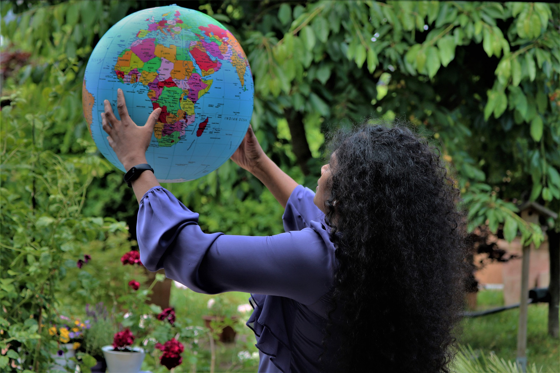 women looking at a globe map